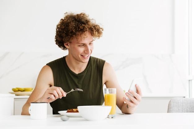 Homem alegre, usando telefone celular e comer bolos
