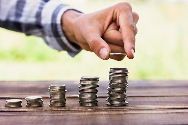 Homem, alinhando moedas no conceito de escala