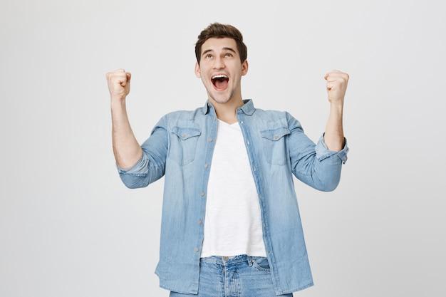 Homem aliviado levantando as mãos e gritando sim