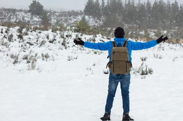 Homem alpinista com casaco azul e mochila, curtindo a neve com os braços abertos no topo de uma montanha. copie o espaço.