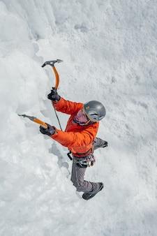 Homem alpinista com ferramentas de gelo machado escalando uma grande parede de gelo. retrato de esportes ao ar livre.
