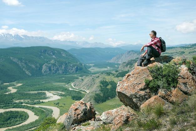 Homem alpinista com mochila sentado no topo do penhasco e olhando o belo vale.