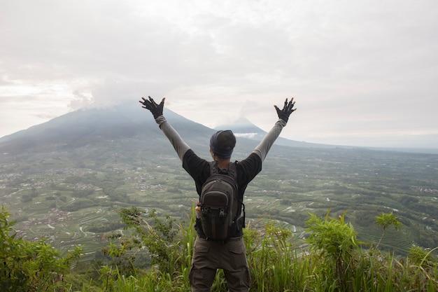 Homem alpinista com uma mochila no topo da montanha, o conceito de motivação e realização de objetivos