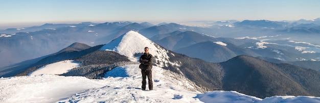 Homem alpinista no topo de uma montanha no inverno
