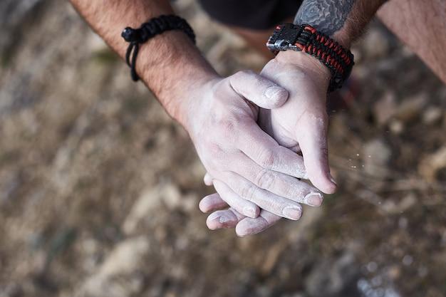 Homem alpinista revestindo as mãos com pó de giz de magnésio e se preparando para escalar. feche as mãos masculinas se preparando para escalar. extreme escala uma rocha em uma corda com o melhor seguro