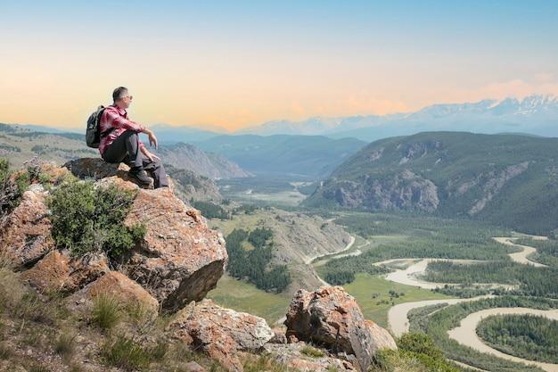 Homem alpinista sentado no penhasco apreciando a vista do vale ao pôr do sol