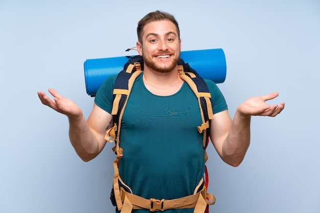 Homem alpinista sobre parede azul com expressão facial chocado