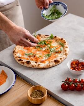 Homem alto colocando rúcula na massa de pizza assada com fatias de salmão defumado