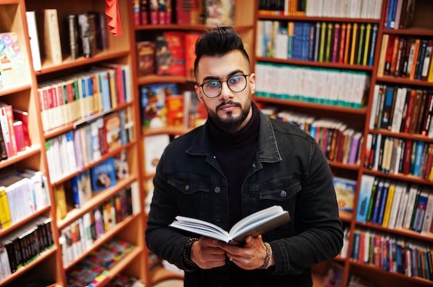 Homem alto inteligente estudante árabe, desgaste na jaqueta jeans e óculos, na biblioteca com o livro nas mãos.