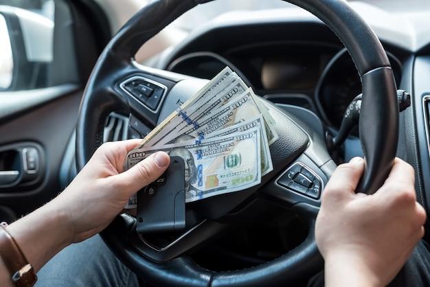 Homem aluga carro para viagem e segurando dolar e chave automática. conceito de finanças