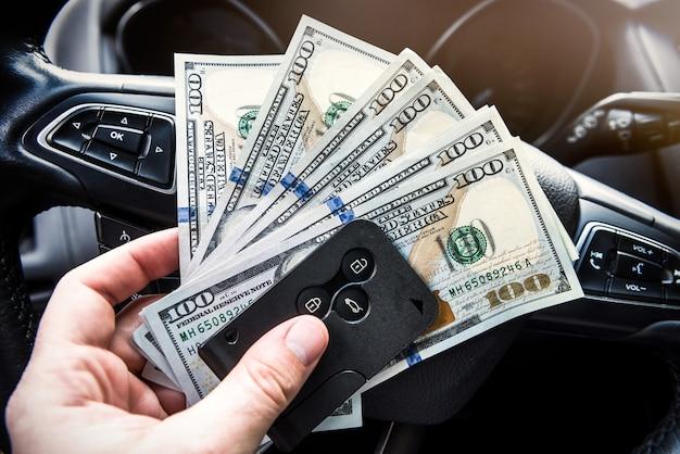 Homem aluga carro para viagem e segurando o conceito de financiamento chave dolar e automóvel