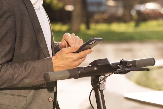 Homem aluga scooter elétrico, transporte ecológico ao ar livre do centro de negócios empresa desconhecida