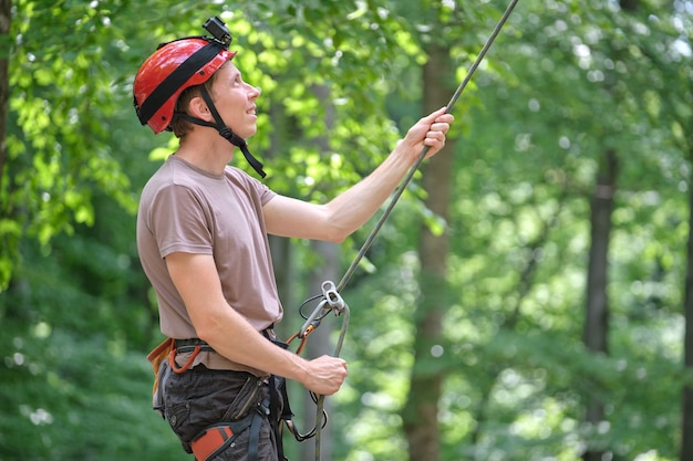 Homem amarra seu parceiro alpinista com dispositivo de amarração e corda. handman do alpinista segurando equipamento para segurança de alpinismo.