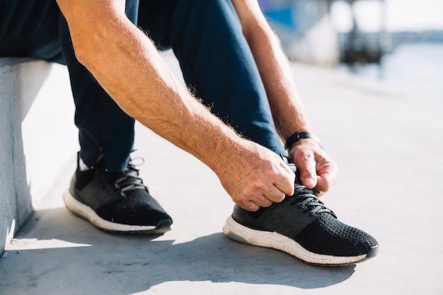 Homem amarrando os cadarços do sapato esquerdo