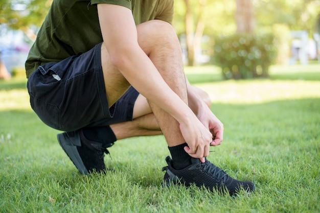 Homem amarrando os sapatos na grama