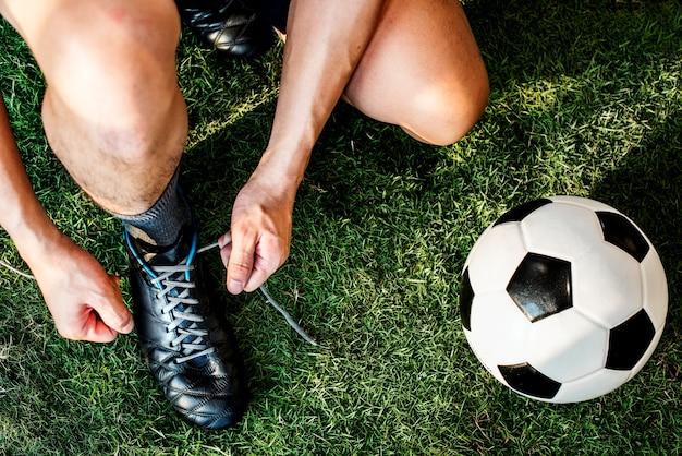 Homem, amarrando, seu, sapatos, e, futebol, conceito