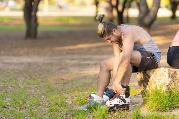 Homem amarrando seus patins enquanto está sentado em uma pedra em um parque