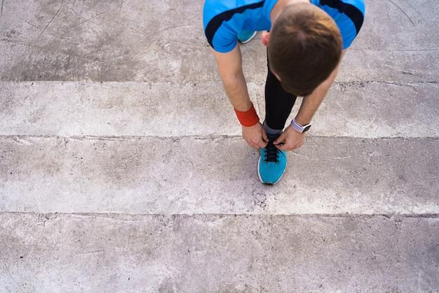 Homem amarrando seus sapatos de desporto em fundo de concreto