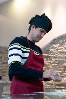 Homem amassando nhoque em roupas de chef
