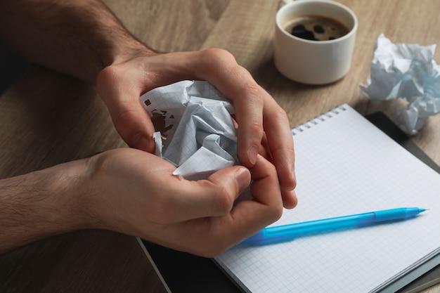 Homem amassando papel na mesa de madeira com caderno e xícara de café, close-up
