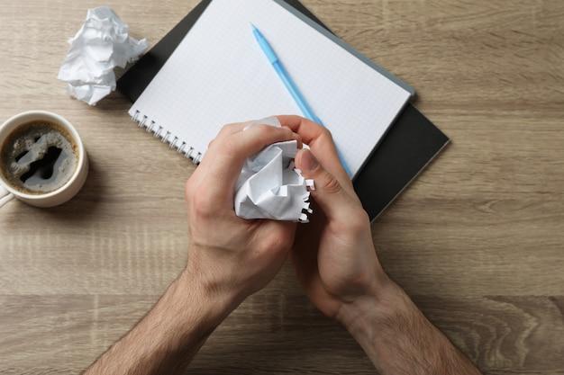Homem amassando papel na mesa de madeira com caderno e xícara de café, vista superior
