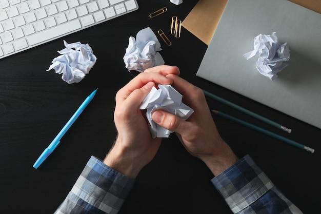 Homem amassando papel na mesa preta com bolas de papel e artigos de papelaria, vista superior