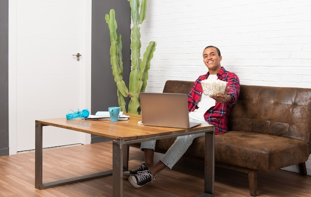 Homem americano africano, com, laptop, em, a, sala de estar, comer, pipocas
