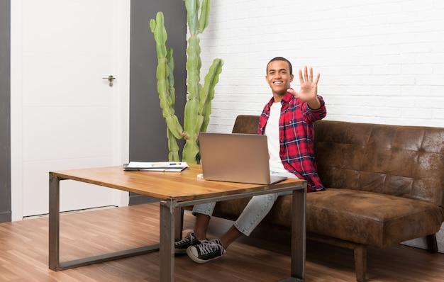 Homem americano africano, com, laptop, em, a, sala de estar, contar, cinco, com, dedos