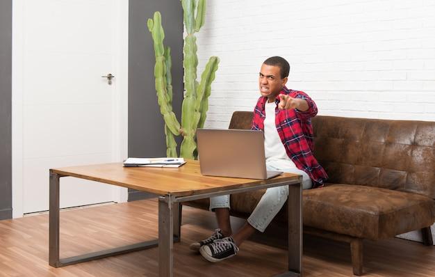 Homem americano africano, com, laptop, em, a, sala de estar, frustrado, por, um, mau, situação, e, apontar, a, frente