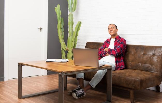 Homem americano africano, com, laptop, em, a, sala de estar, olhar, sorrindo