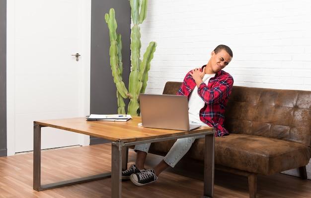 Homem americano africano, com, laptop, em, a, sala de estar, sofrimento, de, dor, em, ombro, para, tendo feito um esforço