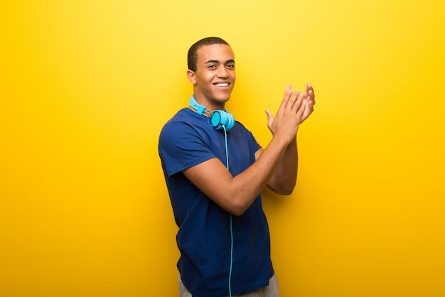 Homem americano africano, com, t-shirt azul, ligado, experiência amarela, aplaudindo, após, apresentação, em, um, conferência