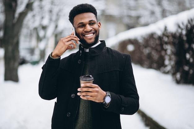 Homem americano africano com telefone e café no inverno ao ar livre