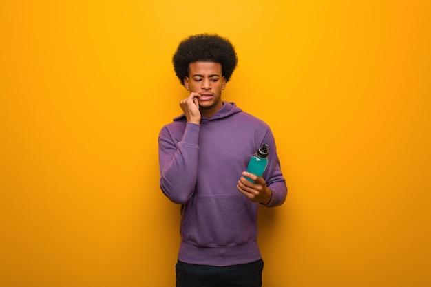 Homem americano africano jovem fitness segurando uma bebida energética, roer unhas, nervoso e muito ansioso