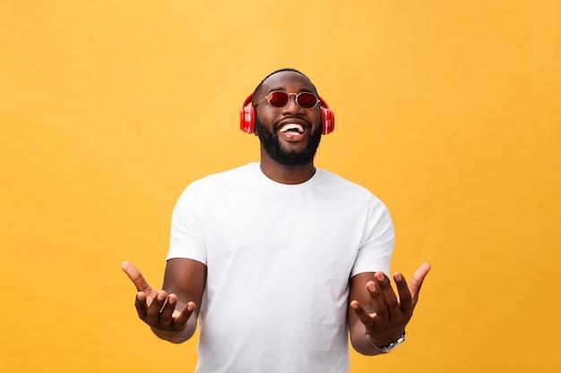 Homem americano africano novo considerável que escuta e que sorri com música em seu dispositivo móvel