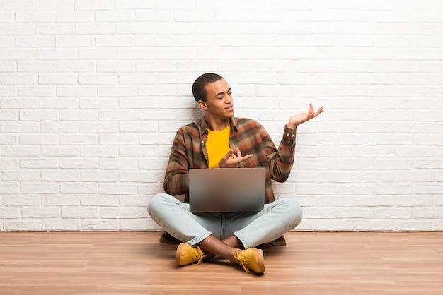 Homem americano africano, sentar chão, com, seu, laptop, estendendo as mãos, para, a, lado, para, convidar, para, venha