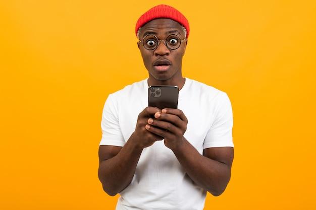 Homem americano bonito em uma camiseta branca com um chapéu vermelho se comunica na rede social em um smartphone com um rosto surpreso