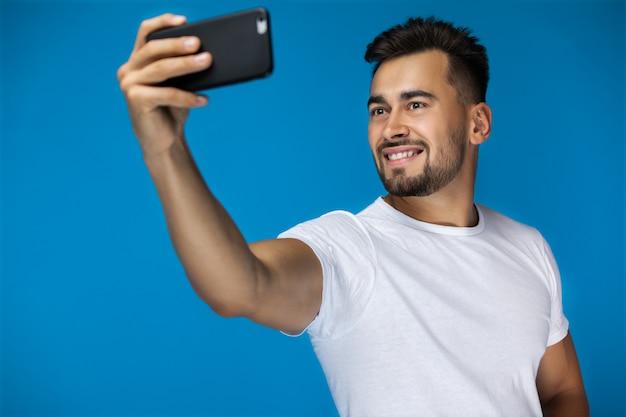 Homem americano bonito leva uma selfie e sorri para a câmera