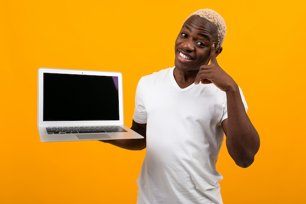 Homem americano, com, cabelo branco, sorrindo, segurando, tela laptop, frente, segurando, polegares cima, perto, templo, amarelo