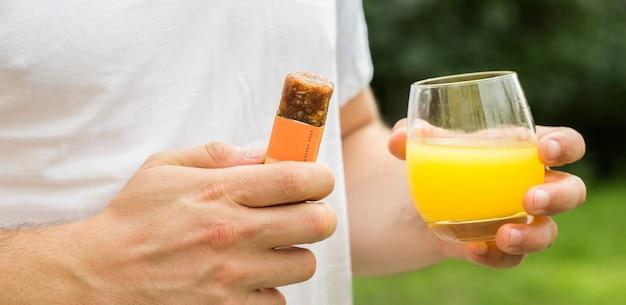 Homem americano comendo barras de cereais energéticos com copo de suco muito feliz apontando com a mão e o dedo para o lado
