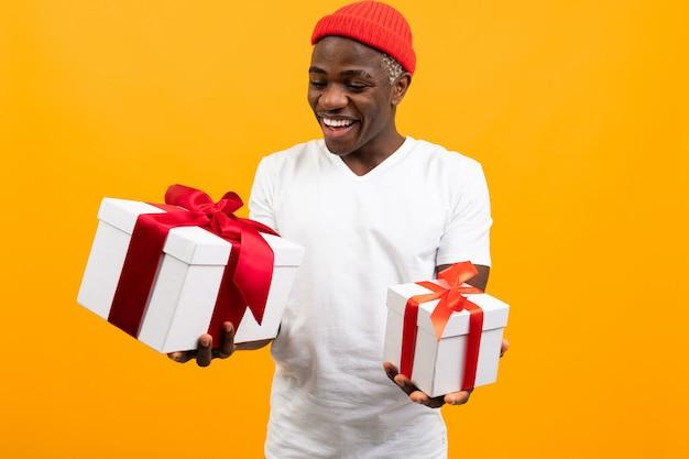 Homem americano engraçado com um sorriso em uma camiseta branca possui duas caixas de presente com fita vermelha em um estúdio amarelo