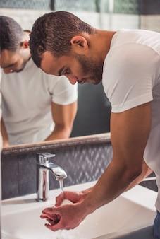 Homem americano está lavando as mãos no banheiro. Foto Premium