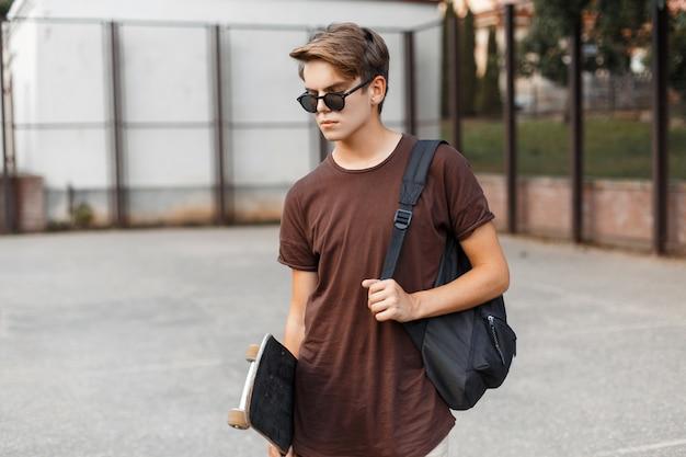 Homem americano jovem hippie com elegantes óculos de sol com uma camiseta de verão e uma mochila preta esportiva com um skate fica em um estádio em um dia quente de verão