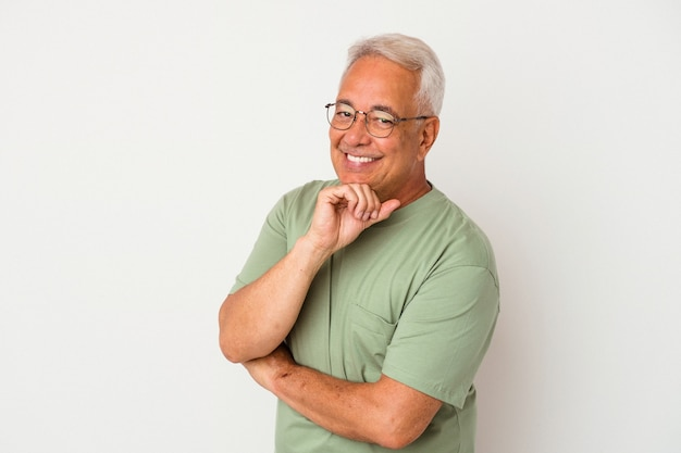 Homem americano sênior isolado no fundo branco, sorrindo feliz e confiante, tocando o queixo com a mão.