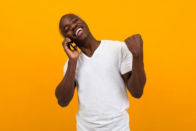 Homem americano sorridente alegre em camiseta branca, falando ao telefone no estúdio laranja limpo