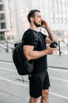 Homem amigável em roupas pretas, falando ao telefone, sorrindo e desviando o olhar. homem de pé perto de blocos de apartamentos, segurando uma garrafa esportiva preta. conceito de vida urbana.