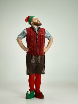 Homem amigável vestido como um gnomo engraçado posando em um cinza isolado