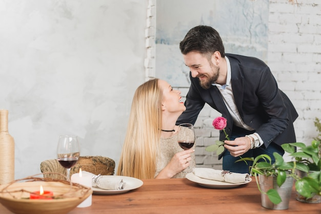 Homem amoroso dando rosa para mulher