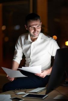 Homem analisando documento à noite