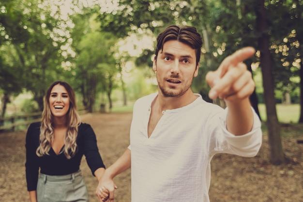 Homem anda pela mão de sua noiva através de um parque, imagem com tons de inverno desbotado.